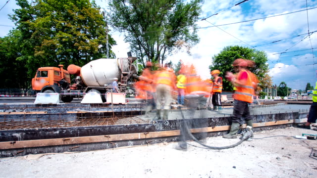 Concrete works for road maintenance construction with many workers and mixer timelapse hyperlapse