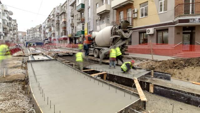 コンクリートは、多くの労働者とミキサー タイムラプスと道路整備工事 - セメント点の映像素材/bロール