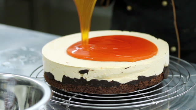 A confectioner adding an orange topping over a cake video