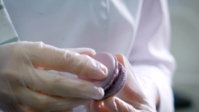 Confectioner connects the two halves of a biscuit between which is a cream. Sweets made by pastry chef in a professional kitchen. Cook makes beautiful desserts with their own hands video