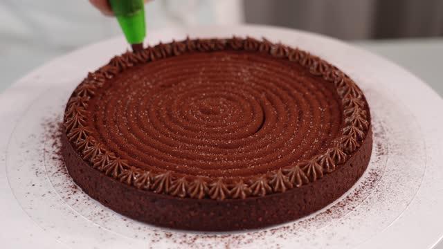 vídeos de stock e filmes b-roll de confectioner decorates tart with chocolate cream on stand - bolo rainha