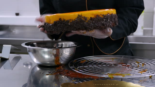 A confectioner decorates the edge of an orange cake with chocolate flakes and puts it on a serving plate in front of the camera video