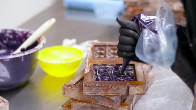 confectioner filling mold by cream at sweet-shop