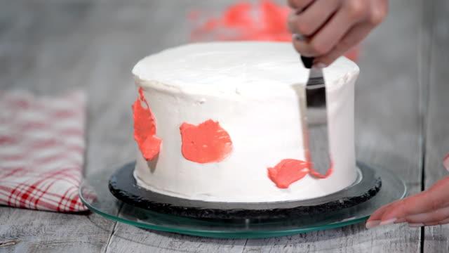 konditor hand ausstrichen rosa crème auf weiß creme von biskuit auf hölzernen drehteller bäckerei küche, vereisung hautnah. - zuckerguss stock-videos und b-roll-filmmaterial