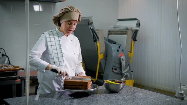 Confectioner with a spatula spread chocolate cream on a freshly baked cake on a professional kitchen in a bakery. Bowl with mastic is on the table video