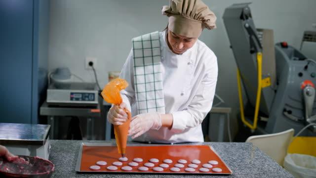 vidéos et rushes de confiseur avec seringue de pâtisserie fait cookies de la même taille avant la cuisson dans la cuisine. dessert de brut sur le pont. ustensiles de cuisine pour la cuisson des gâteaux. aide-cuisinier propre bol de crème - boulanger