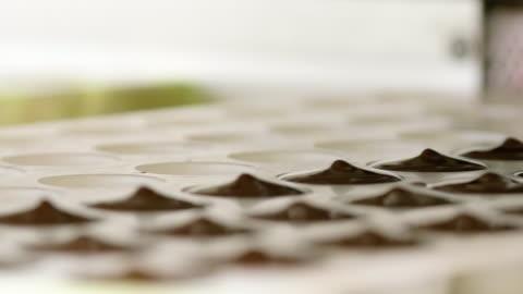 vídeos y material grabado en eventos de stock de confitería. línea de producción para la producción de chocolates. máquina de chocolate - verter en el molde - dulces