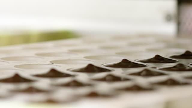 confetteria. linea di produzione per la produzione di cioccolatini. macchina per cioccolato - versando nello stampo - dolci video stock e b–roll