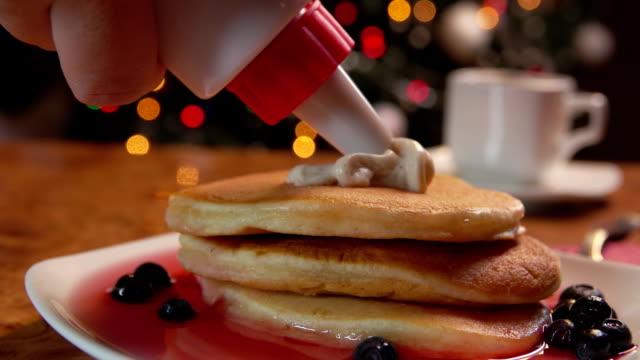 vídeos de stock e filmes b-roll de confectionery syringe puts cream in stack of pancakes - christmas cake