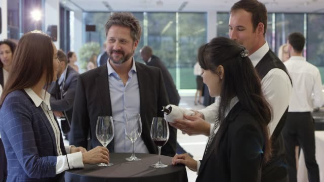 konferensdeltagare chatta på tabellen i lobbyn på konferenscentret och dricka ett glas vin - affärskonferens bildbanksvideor och videomaterial från bakom kulisserna