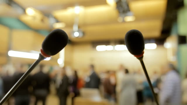 konferenzmikrofonen auf dem hintergrund der menschen - konferenz stock-videos und b-roll-filmmaterial