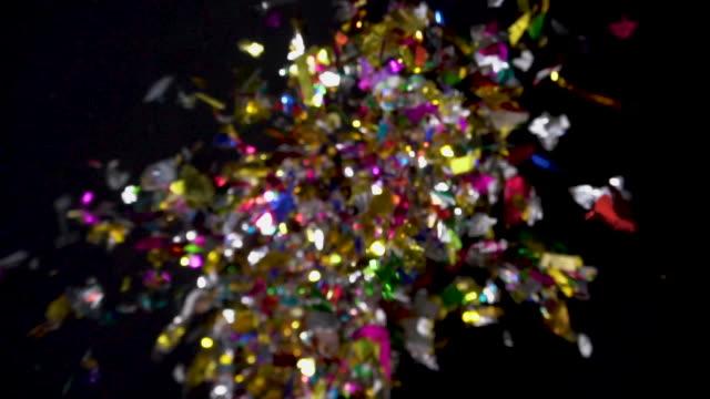Confetti explosion to camera on black background