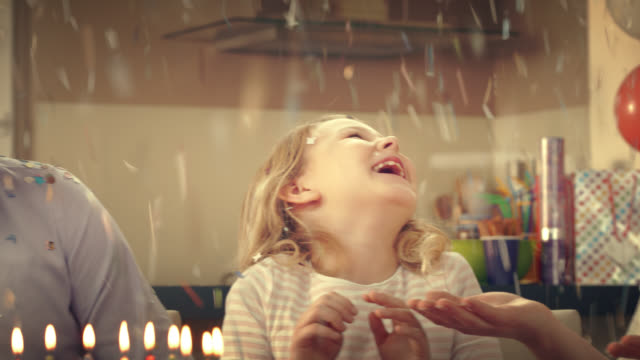 Confetti falling on the birthday girl blowing out the candles video