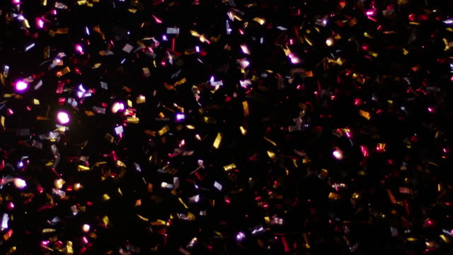 Confetti Isolated on Black Background Confetti fired in the air during a party. Only confetti on black background of the night. Falling metallic glitter foil confetti multicolor in black background. uk border stock videos & royalty-free footage