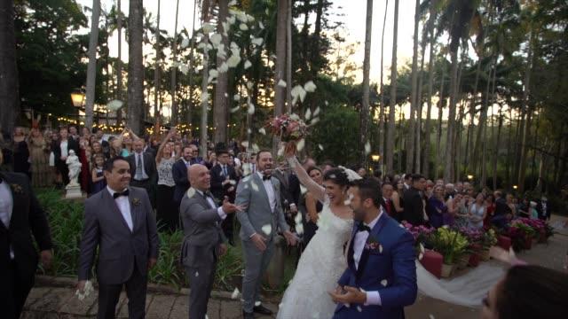 confetti throwing on happy newlywed couple - video di matrimonio video stock e b–roll