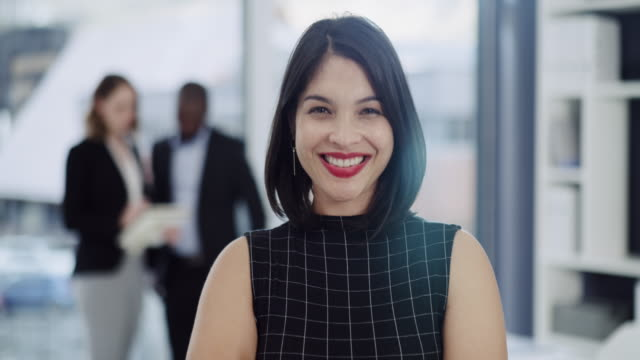 Confidence gives you power 4k video footage of a young businesswoman standing in an office with her colleagues in the background employee stock videos & royalty-free footage