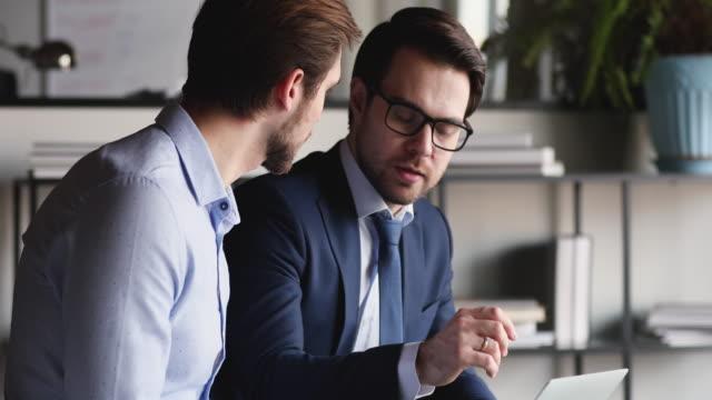 vídeos de stock e filmes b-roll de confident adviser consulting client showing online project presentation on computer - conselho