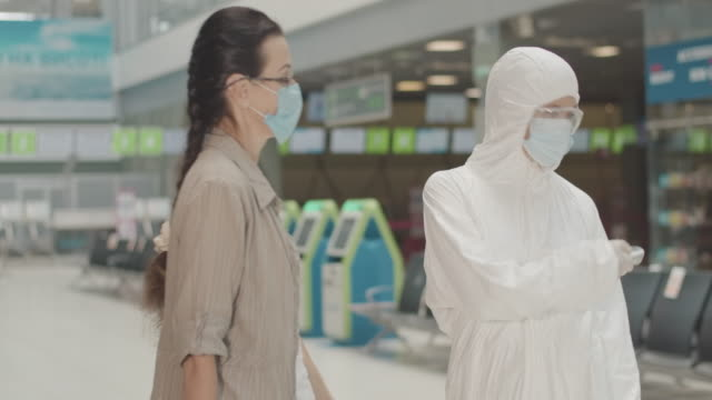 vídeos de stock e filmes b-roll de confident airport employee in protective suit calling for passenger, measuring mid-adult woman's temperature and letting tourist enter terminal. covid-19 pandemic restrictions. cinema 4k prores hq. - mulher deixar ir