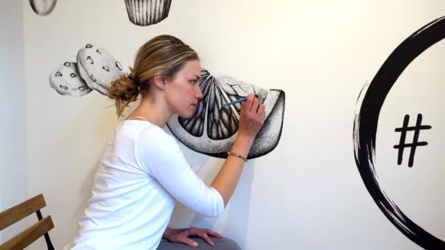 självsäker och koncentrerad konstnär avslutar sin väggmålning konstverk - väggmålning bildbanksvideor och videomaterial från bakom kulisserna