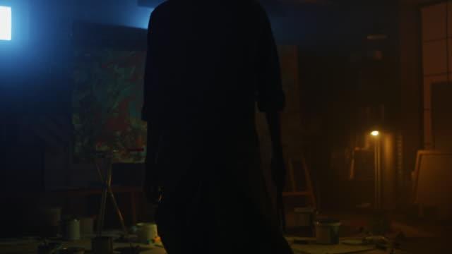 vidéos et rushes de artiste féminine confiante et déterminée marche à la toile et commence à travailler sur une peinture à l'huile abstraite moderne utilisant le pinceau. dans le studio créatif large picture stands on easel illuminated. suite back view slow motion shot - toile à peindre