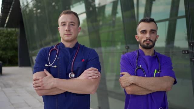 anestesisti fiduciosi si trovano orgogliosamente di fronte alla moderna clinica medica dopo il loro lungo turno - fianco a fianco video stock e b–roll