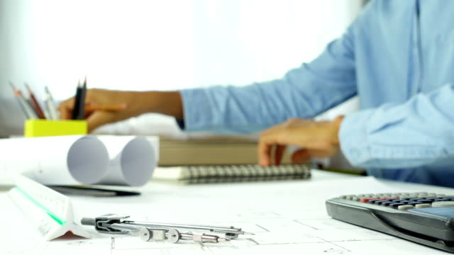självsäker arkitekt mannen i fritidskläder som arbetar på skrivbord i suddig. begreppet byggnad arbetar på hus-projektet. - linjerat papper bakgrund bildbanksvideor och videomaterial från bakom kulisserna