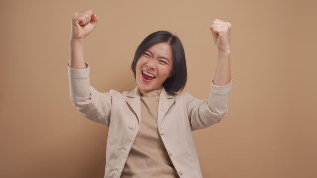 Confident asian business woman happy and make winning gesture standing isolated over beige background. 4K video
