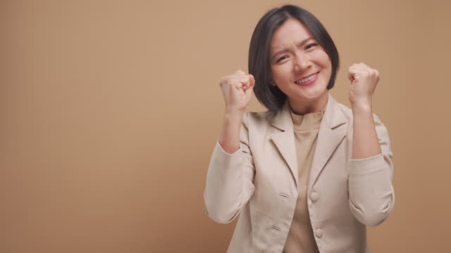 Confident asian business woman happy and make winning gesture with copy space isolated over beige background. 4K video