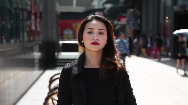 confident asian chinese lady businesswoman walking on the busy streets - etnia malese video stock e b–roll