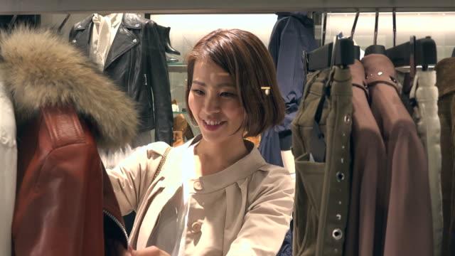 自信を持ってアジア女性ファッション ストア内部モールでショッピング - 小売り点の映像素材/bロール