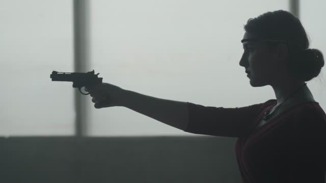 säker attraktiv kvinna i snygg röd klänning siktar en pistol i en övergiven dammig byggnad - dirty money bildbanksvideor och videomaterial från bakom kulisserna