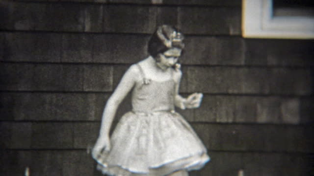1936: Confident ballet girl solo dancing in front of house.