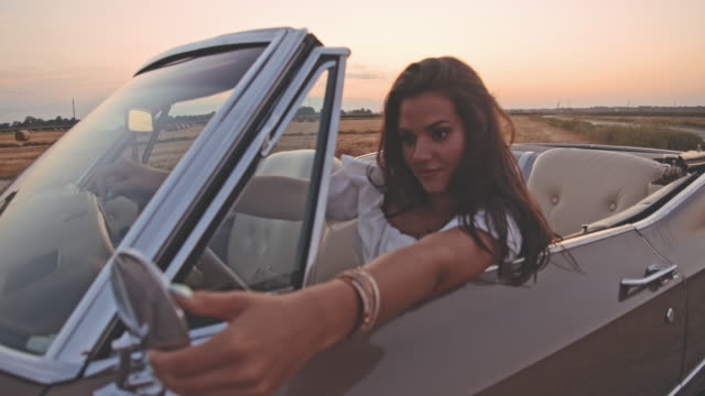 SLO MO Confident, beautiful young woman looking in convertible side-view mirror Confident, beautiful young woman looking in convertible side-view mirror. Slow Motion. vanity stock videos & royalty-free footage