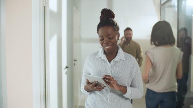 Confident Black Businesswoman Walking along Office Corridor