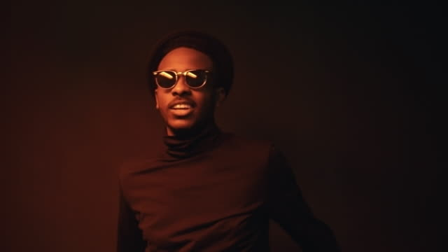 Confident Black Man Posing in Red Lighting Low-key portrait shot with use of red lighting: confident black man in hat and sunglasses standing in dark studio and posing for camera low lighting stock videos & royalty-free footage