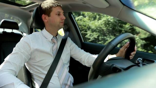confident businessman driving car in countryside - сельская дорога стоковые видео и кадры b-roll