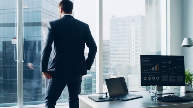 Confident Businessman in a Suit Contemplating Business Deal in His Office, Stands up from His Desk and Walks to a Window to Think. Window Has Panoramic View on Big City Business District. Confident Businessman in a Suit Contemplating Business Deal in His Office, Stands up from His Desk and Walks to a Window to Think. Window Has Panoramic View on Big City Business District. standing stock videos & royalty-free footage
