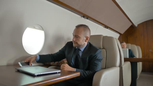 Seguro de hombre de negocios en traje formal de viaje en su jet privado y chat en el teléfono celular - vídeo