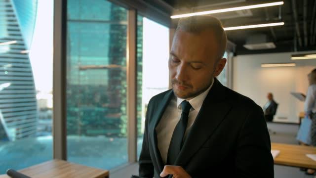 vidéos et rushes de homme d'affaires confiant dans le bureau openspace appelant à son partenaire d'affaire - homme slip