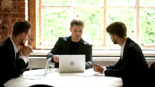 Confident businessman presenting documents to clients, discussing contract with investors video