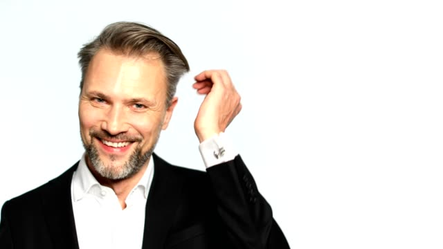 Confident businessman smiling and caressing hair Portrait of confident businessman caressing his hair. Close-up of mature male professional is smiling on white background. He is wearing suit. 50 54 years stock videos & royalty-free footage