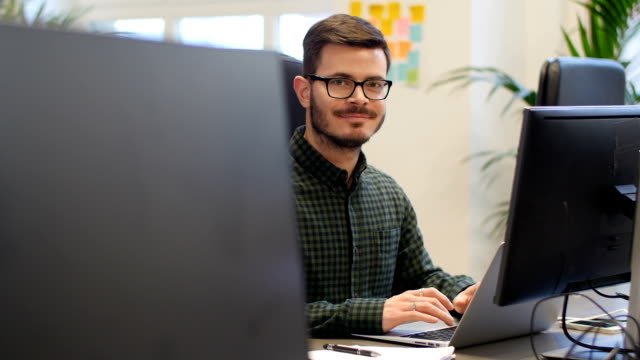 Confident businessman smiling while using laptop video