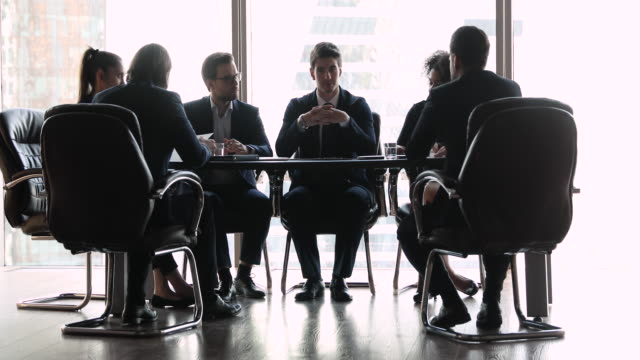 Confident businessman speak to diverse business people at conference table