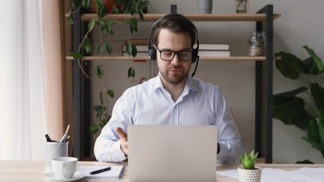自信に満ちたビジネスマンは、ビデオ会議アプリを使用して遠くにクライアントと話します - オンライン会議点の映像素材/bロール