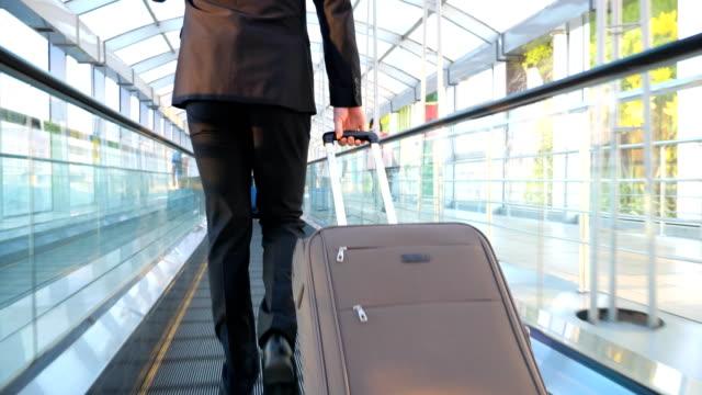 stockvideo's en b-roll-footage met zelfverzekerde zakenman wandelend door glazen hal van terminal met zijn bagage en praten op telefoon. succesvolle ondernemer met werk gesprek wordt op weg naar de vlucht. slow motion achteraanzicht - zakenreis