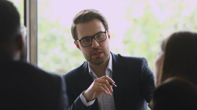vidéos et rushes de l'homme d'affaires confiant portent le discours de costume aux clients de consultation de réunion de groupe - expliquer