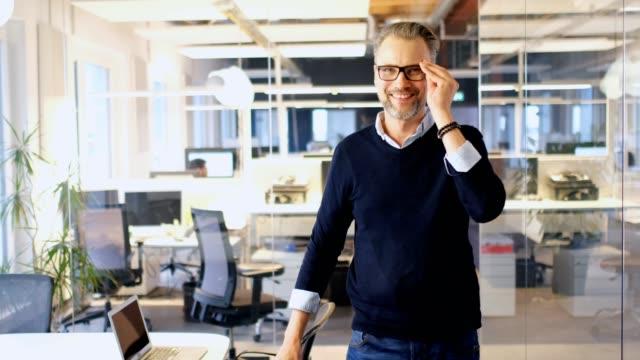 självsäker affärsman bär glasögon i office - medelålders män bildbanksvideor och videomaterial från bakom kulisserna