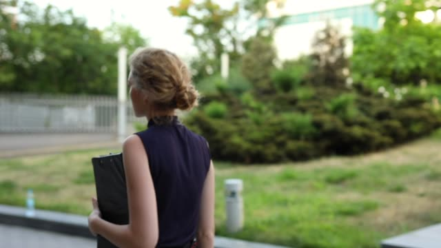 zuversichtliche geschäftsfrau mit ordner aus dem büro - weibliche führungskraft stock-videos und b-roll-filmmaterial