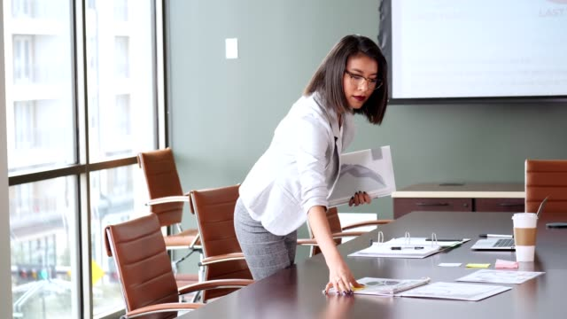 Confident businesswoman prepares conference room for meeting