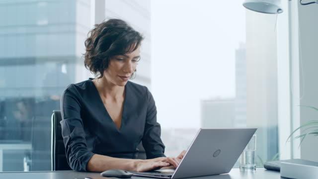 zuversichtlich geschäftsfrau sitzt an ihrem schreibtisch und arbeiten auf einem laptop in ihrem modernen büro. elegante schöne frau wichtige arbeit tun. in der fensteransicht großen geschäftsviertel der stadt. - weibliche angestellte stock-videos und b-roll-filmmaterial
